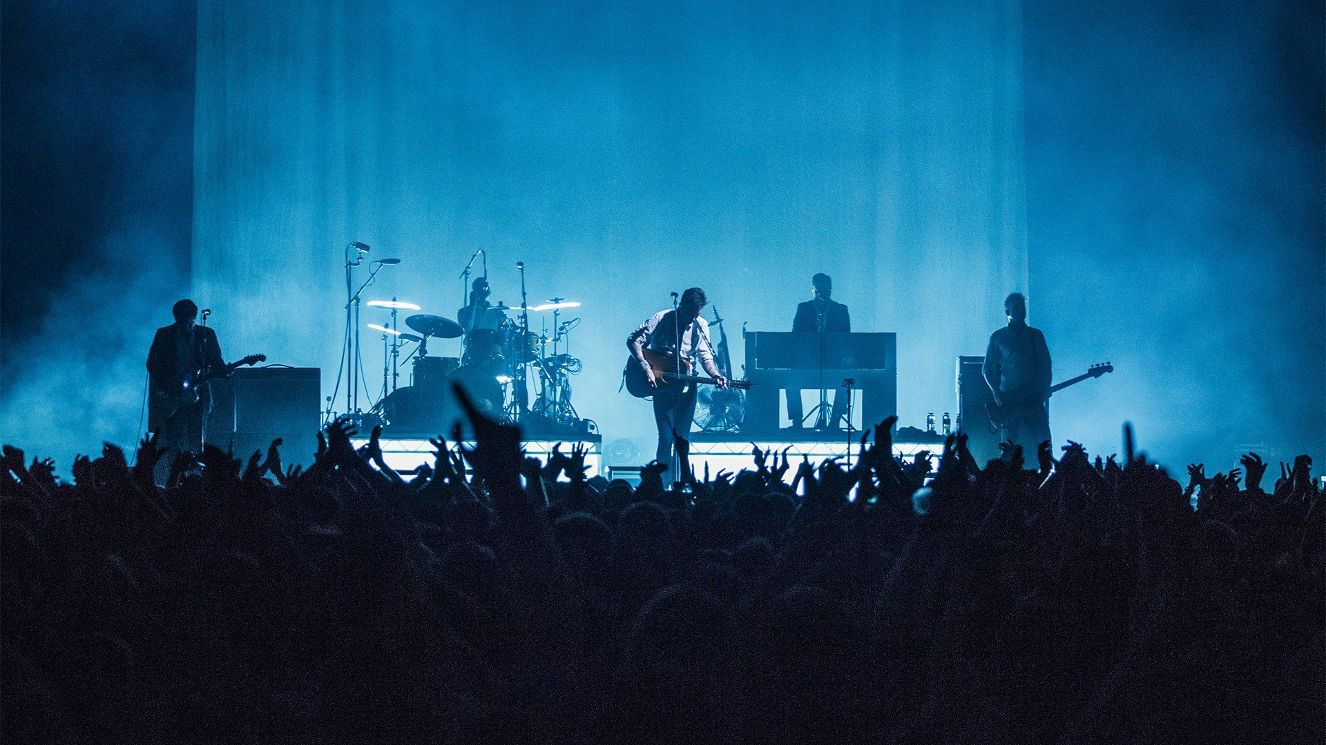A band play on an atmospheric stage at night, with smoke and blue light, and hands in the foreground. Photo by Ben Morse.